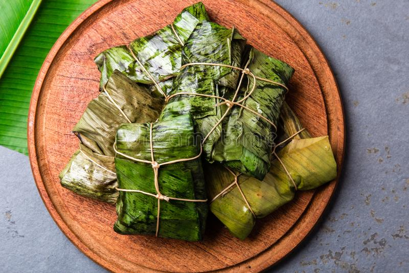 KOLUMBIJSKI, ŚRODKOWO-AMERYKAŃSKI jedzenie, Tamales zawijający w bananowym drzewku palmowym opuszczają na drewnianych talerzach,  obraz royalty free