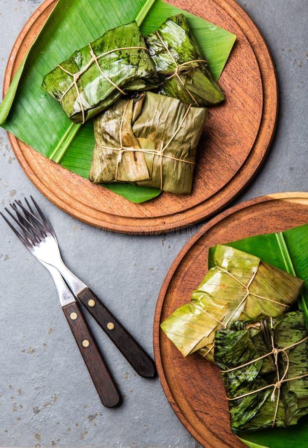 KOLUMBIJSKI, ŚRODKOWO-AMERYKAŃSKI jedzenie, Tamales zawijający w bananowym drzewku palmowym opuszczają na drewnianych talerzach,  zdjęcia royalty free