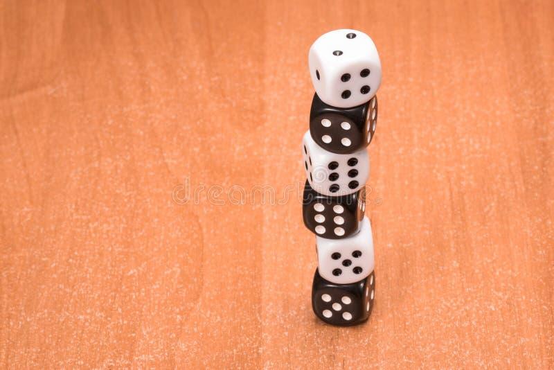Kolumna kostka do gry czarny i biały na drewnianym tle obraz stock