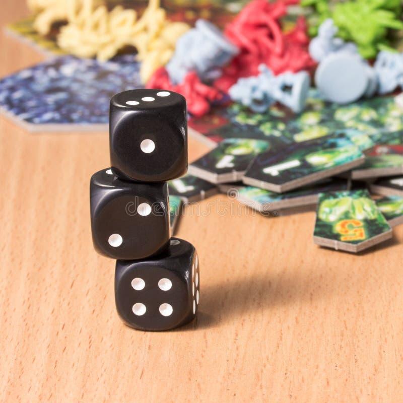 Kolumna trzy ciemnego kostka do gry na rozmytym tle gra planszowa zdjęcia stock