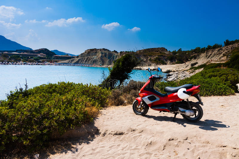 Kolymbia beach with motorcycle. Kolymbia beach with the rocky coast in Greece with red motorcycle stock images