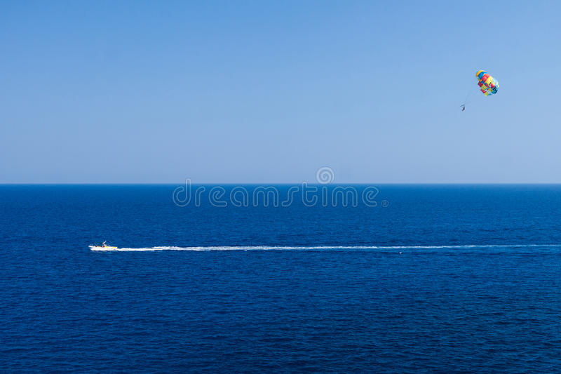Kolymbia beach with the rocky coast in Greece. Parasailing is a popular pastime in many resorts around the world. The active form of relaxation royalty free stock photo