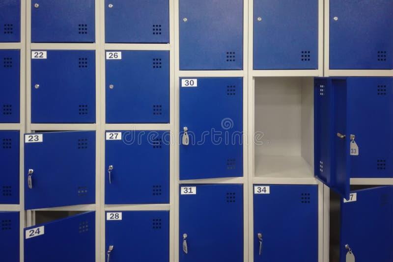 Komórki w błękitnym koloru bagażu magazynie z kluczami i jeden otwarte drzwiego tłem obraz stock