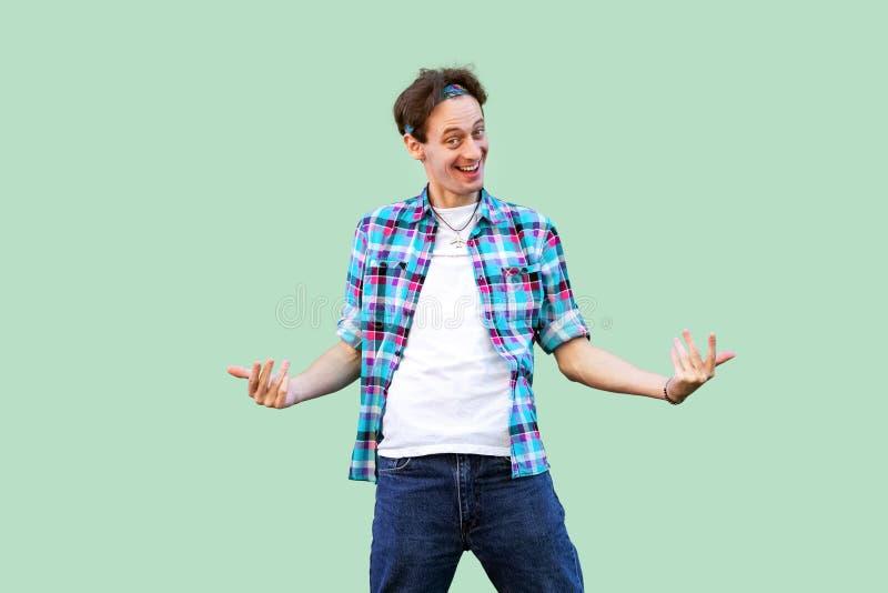 Kom aan me Portret van de grappige jonge mens in toevallige blauwe geruite overhemd en hoofdband status bekijkend camera en uitno royalty-vrije stock afbeelding