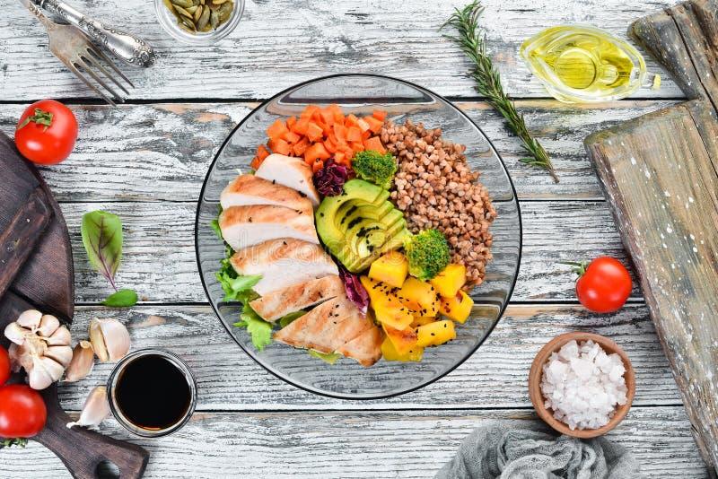 Kom Boedha Boekweit, pompoen, kippenfilet, avocado, wortelen Op een witte houten achtergrond stock foto