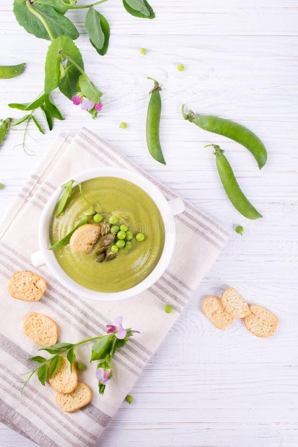 Kom de eigengemaakte groene die soep van de de lenteerwt met pompoenzaden wordt bedekt, croutons Op witte achtergrond royalty-vrije stock afbeeldingen