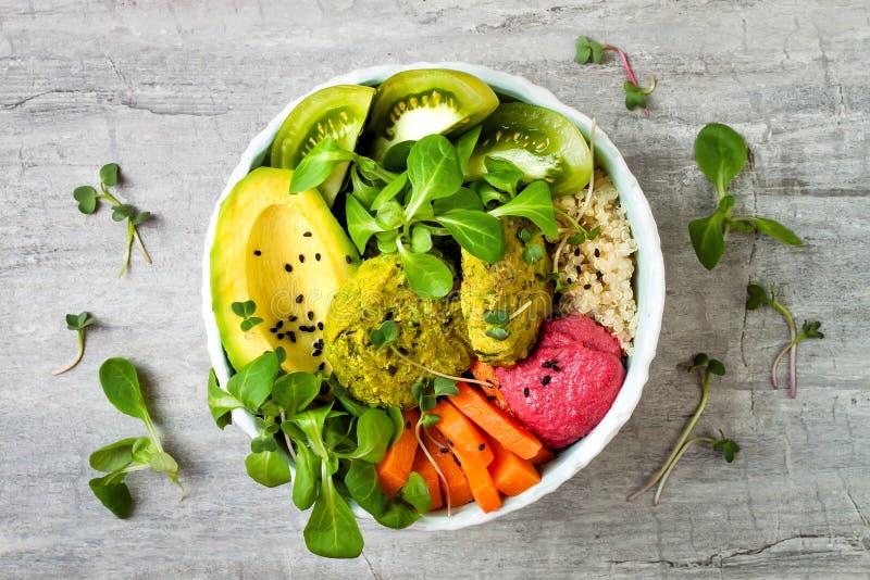 Kom de van het Middenoosten van stijlboedha met groene falafel, quinoa, butternut plet, tomaten, avocado, bietenhummus en tahinis royalty-vrije stock afbeeldingen