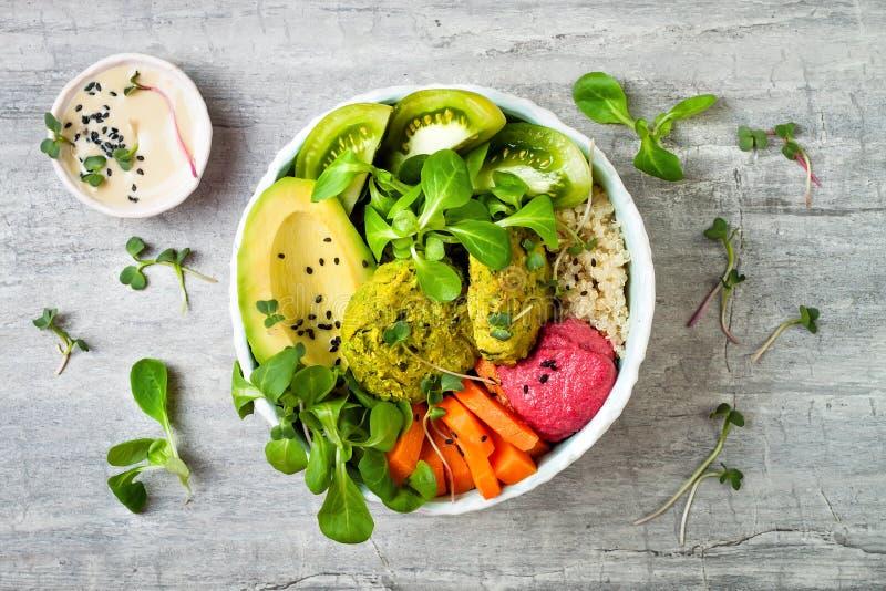 Kom de van het Middenoosten van stijlboedha met groene falafel, quinoa, butternut plet, tomaten, avocado, bietenhummus en tahinis stock foto