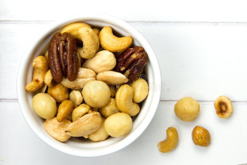 Kom die met noten en een paar noten naast het wordt gevuld royalty-vrije stock foto