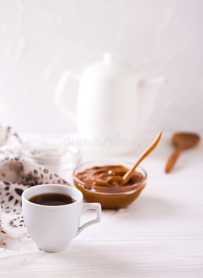 Kom eigengemaakte gesmolten karamelsaus en koffie royalty-vrije stock afbeeldingen