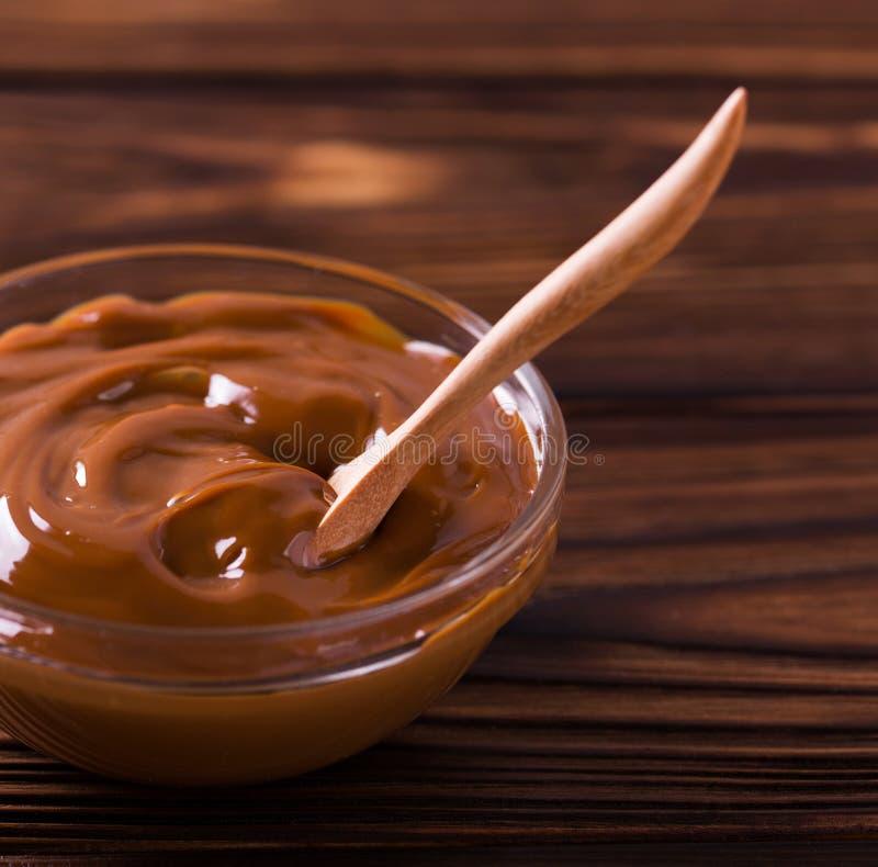 Kom eigengemaakte gesmolten karamelsaus op houten lijst royalty-vrije stock afbeelding