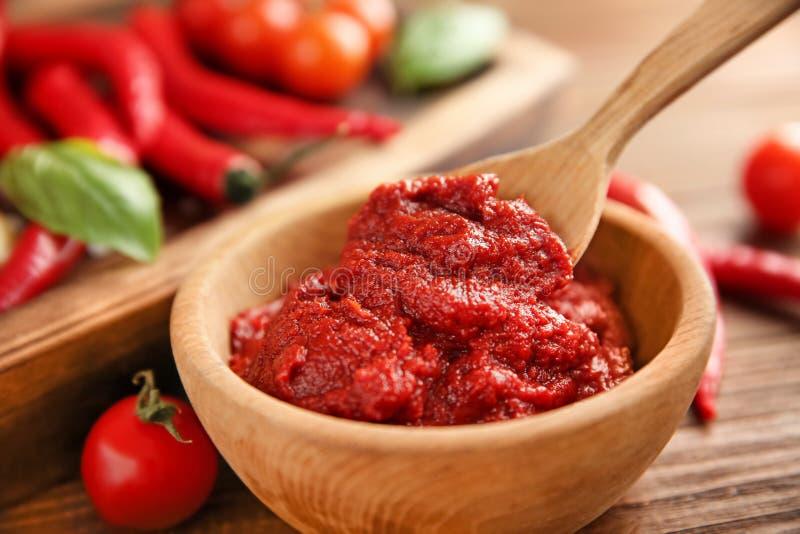 Kom en lepel met rode saus, close-up royalty-vrije stock foto's
