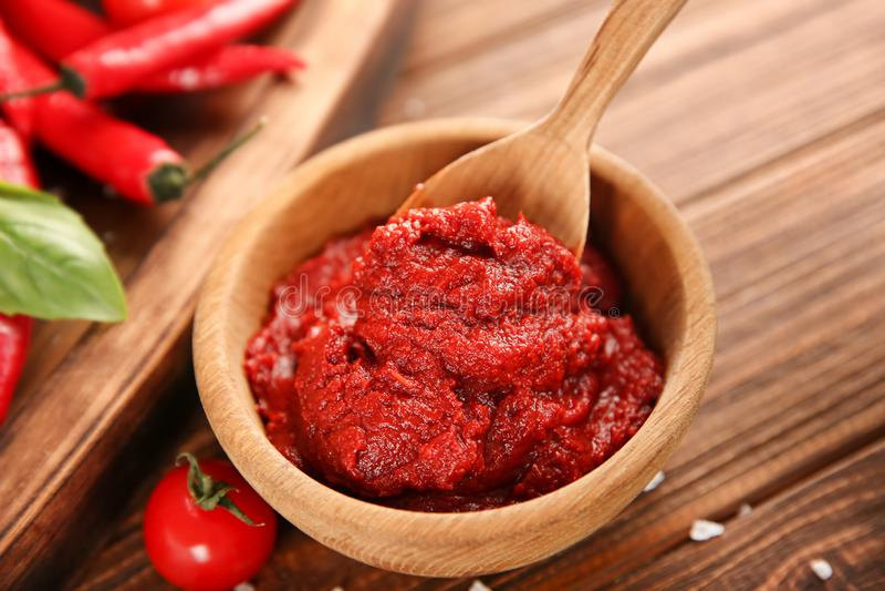 Kom en lepel met rode saus, close-up stock afbeelding