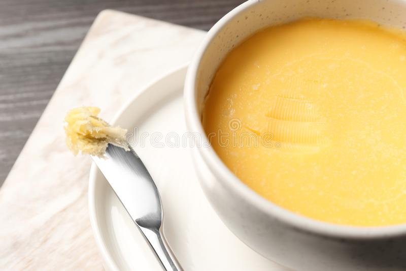Kom en mes met smeltende boter op lijst, close-up royalty-vrije stock fotografie