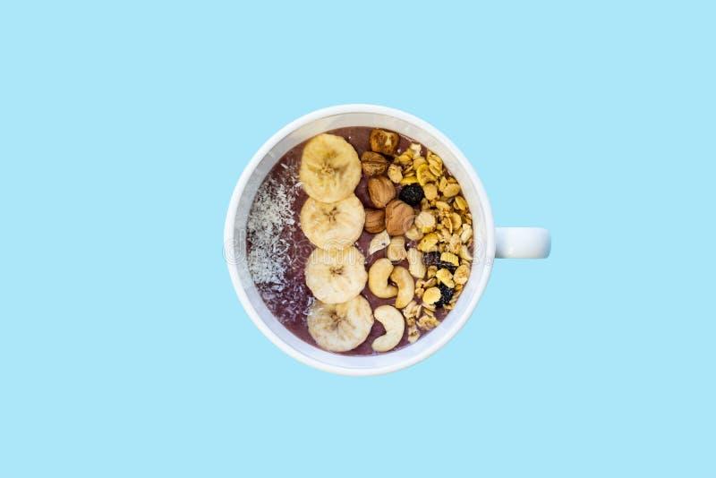 Kom fruit smoothie met noten en banaan, hoogste mening Vlak leg van een acaikom met graangewassen, cachou en hazelnoten in blauwe stock afbeelding