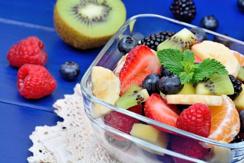 Kom gezonde verse fruitsalade op houten achtergrond royalty-vrije stock afbeelding