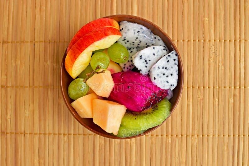 Kom gezonde verse fruitsalade op houten achtergrond stock afbeeldingen