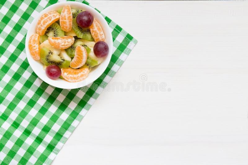 Kom gezonde verse fruitsalade op witte houten achtergrond, hoogste mening, exemplaarruimte royalty-vrije stock foto