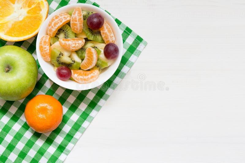 Kom gezonde verse fruitsalade op witte houten achtergrond, hoogste mening, exemplaarruimte stock afbeelding