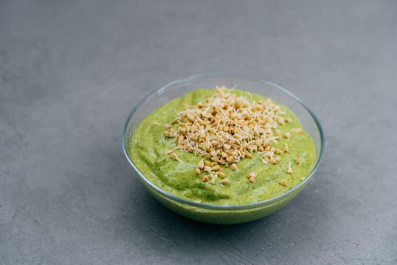 Kom groene smoothie die van spinazie met boekweitspruiten wordt gemaakt op grijze achtergrond Veganistvoedsel Gezond het eten en  stock foto's