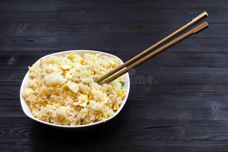 Kom met Fried Rice met eetstokjes op donkere lijst stock afbeeldingen