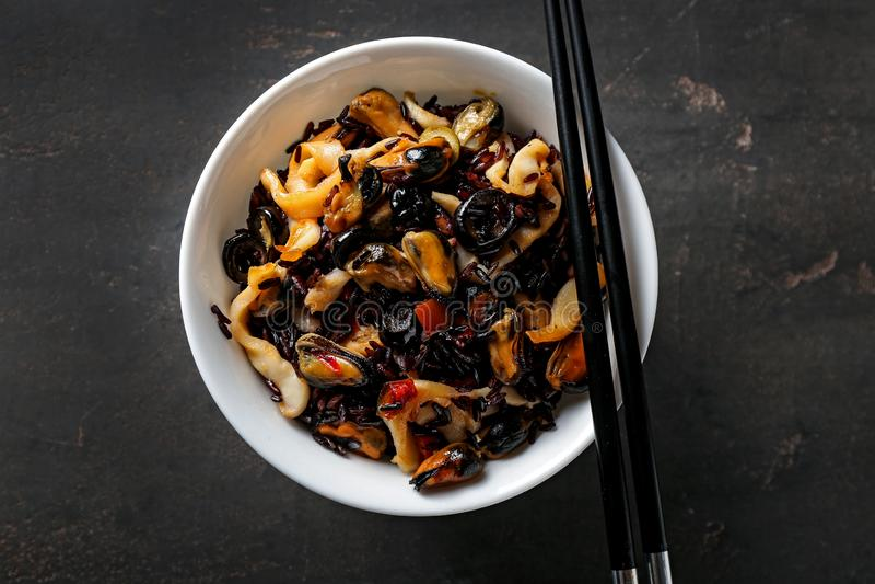Kom met gekookte rijst en zeevruchten op donkere lijst stock afbeeldingen