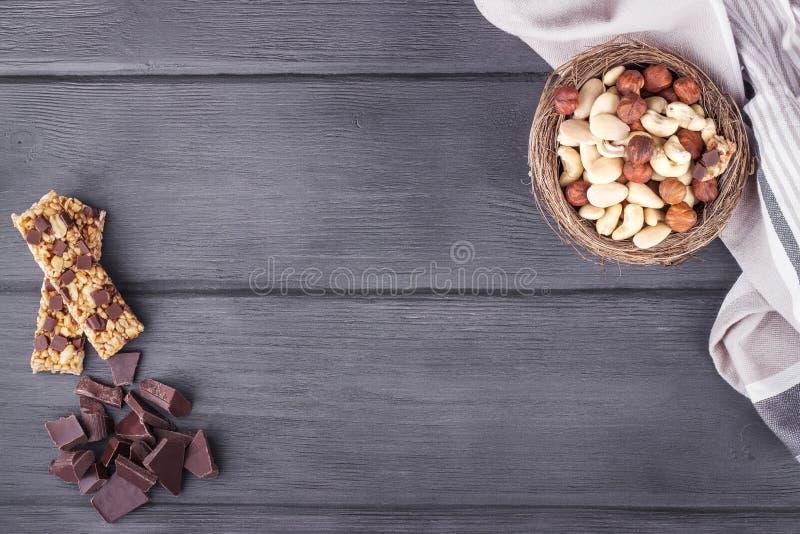 Kom met gemengde noten, granolabars, chocolade en keukenhanddoek royalty-vrije stock afbeelding