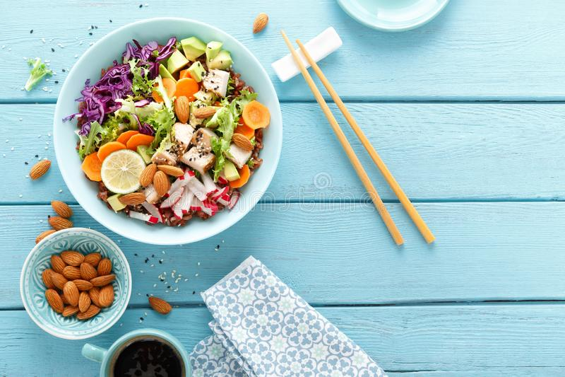 Kom met geroosterd kippenvlees, ongepelde rijst en verse groentesalade van avocado, radijs, koolboerenkool, wortel, en slabladere stock fotografie