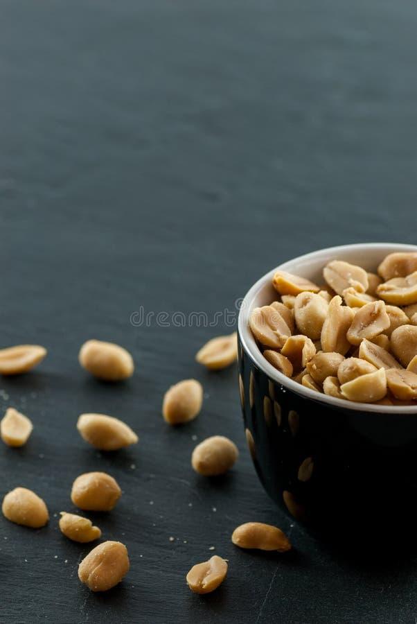 Kom met geroosterde en gezouten pinda's op een lei met exemplaarruimte stock afbeeldingen