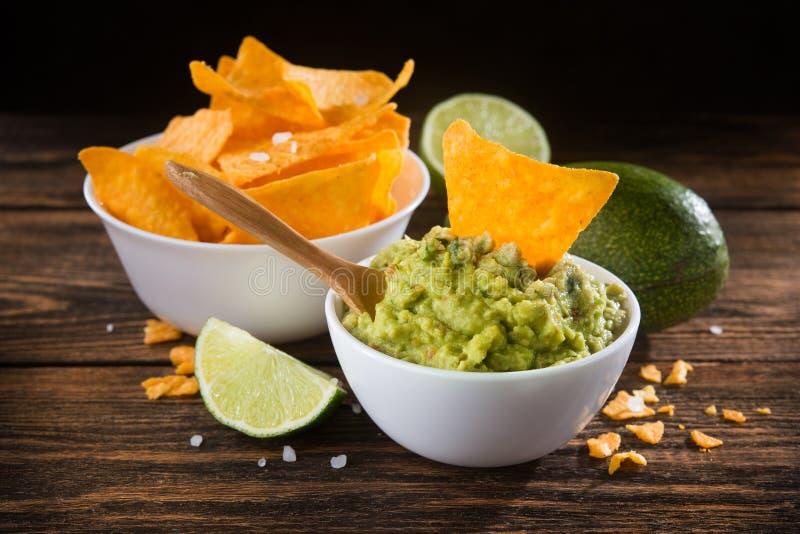 Kom met guacamolesaus en nachosspaanders royalty-vrije stock foto's