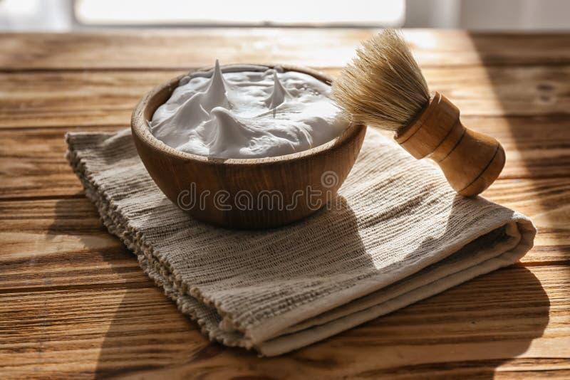 Kom met het scheren van schuim en borstel op houten lijst stock foto's