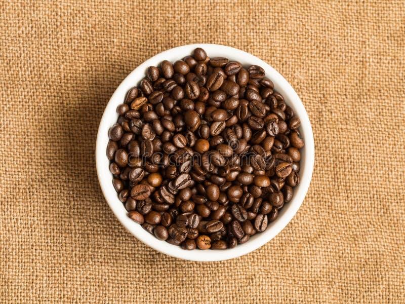 Kom met koffiebonen, op juteachtergrond De mening van hierboven, sluit omhoog royalty-vrije stock afbeeldingen