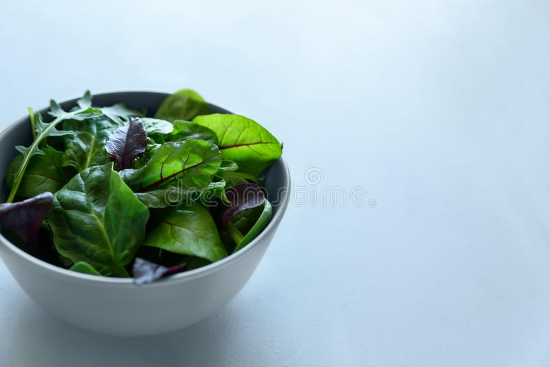 Kom met mengelings verse bladeren van arugula, spinazie en bietenbladeren op grijze houten achtergrond Vegetarisch voedselconcept royalty-vrije stock fotografie