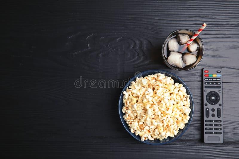 Kom met popcorn, glas bevroren kola en verre TV stock afbeeldingen
