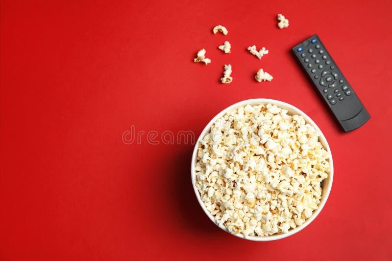 Kom met popcorn, TV ver en ruimte voor tekst op kleurenachtergrond, hoogste mening stock fotografie