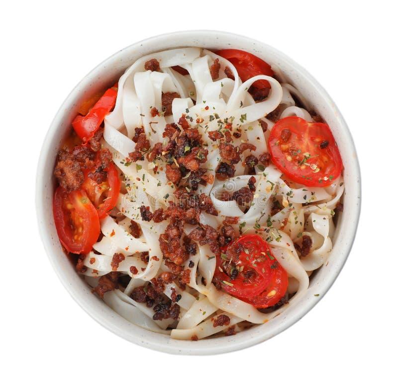 Kom met rijstnoedels, vlees en tomaten op witte, hoogste mening stock fotografie