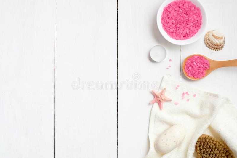Kom met roze bad zoute, houten lepel, handdoek, zeepzeester, kuuroordborstel op houten oppervlakte Het concept van de kuuroordpro royalty-vrije stock afbeelding