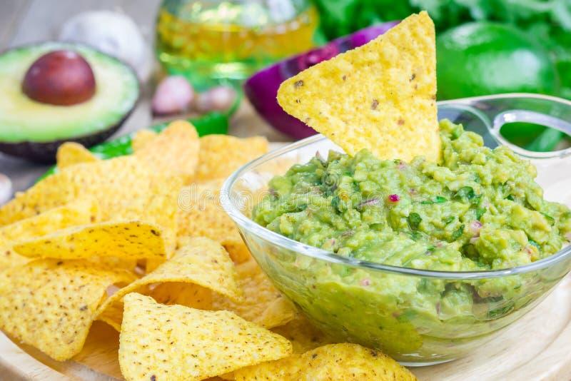 Kom met ruige die guacamole met nachos wordt gediend stock afbeelding