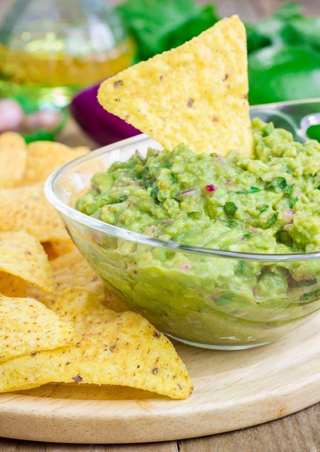 Kom met ruige die guacamole met nachos wordt gediend royalty-vrije stock afbeeldingen