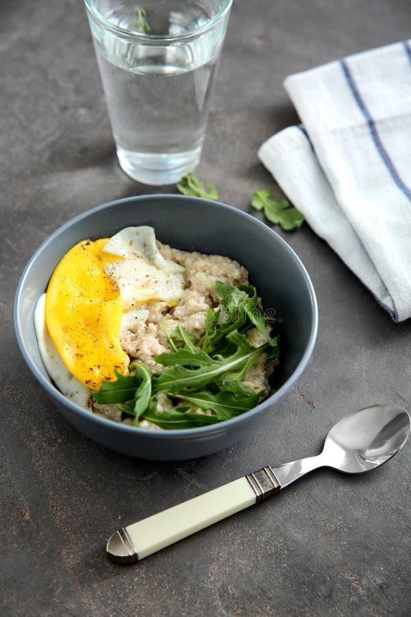 Kom met smakelijk havermeel, gebraden ei en arugula op lijst stock foto