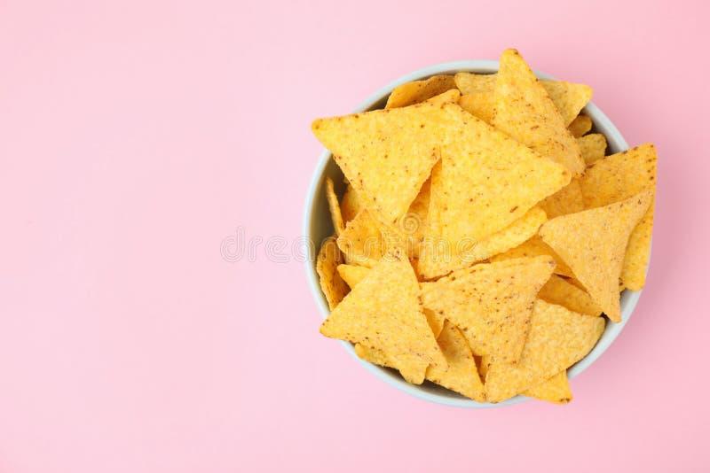 Kom met smakelijke Mexicaanse nachosspaanders op roze achtergrond, hoogste mening royalty-vrije stock afbeelding