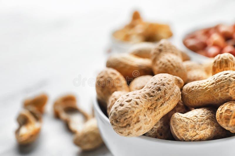Kom met smakelijke pinda's op lijst, close-up stock afbeelding