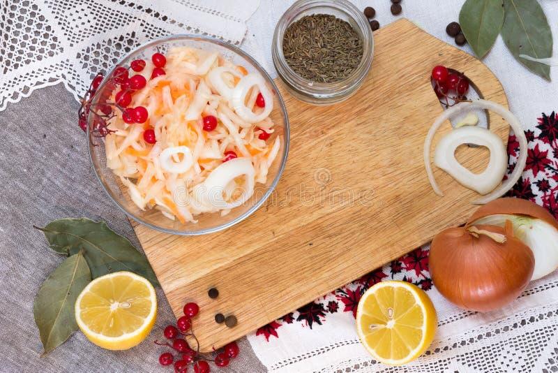Kom met zuurkool en groenten in het zuuringrediënten stock foto
