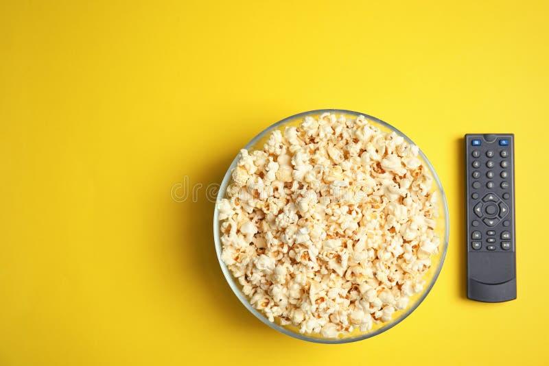 Kom popcorn, TV ver en ruimte voor tekst op kleurenachtergrond, hoogste mening stock afbeelding