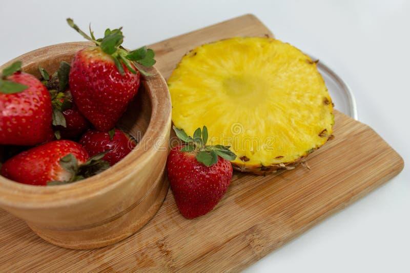 Kom van aardbeien met ananasplak op een hakbord royalty-vrije stock afbeelding