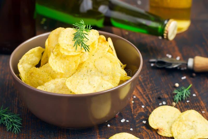 Kom van chips met dille op bierachtergrond royalty-vrije stock afbeelding