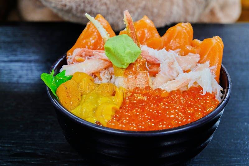 Kom van de premie dient de vastgestelde rijst met verse ruwe zeevruchtenmengeling, krab, zalm, zalmeieren, uni samen met wasabi,  royalty-vrije stock foto's