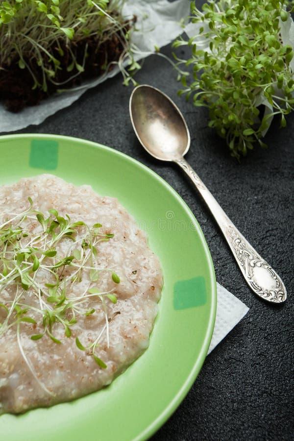 Kom van eigengemaakt havermeel met micro- greens op een rustieke lijst, gezond ontbijtvoedsel stock foto's