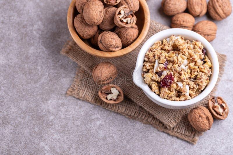 Kom van eigengemaakte granola met noten en rozijnen op grijze leiachtergrond stock afbeelding