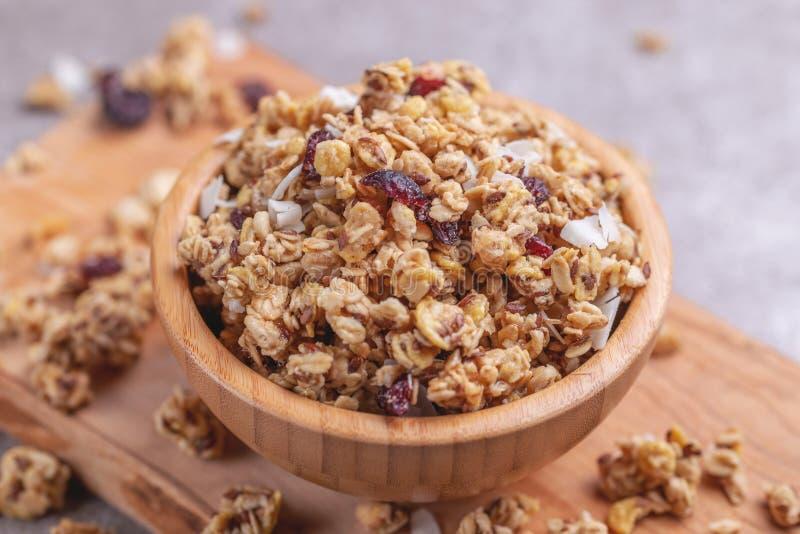 Kom van eigengemaakte granola met noten en rozijnen op grijze leiachtergrond royalty-vrije stock fotografie